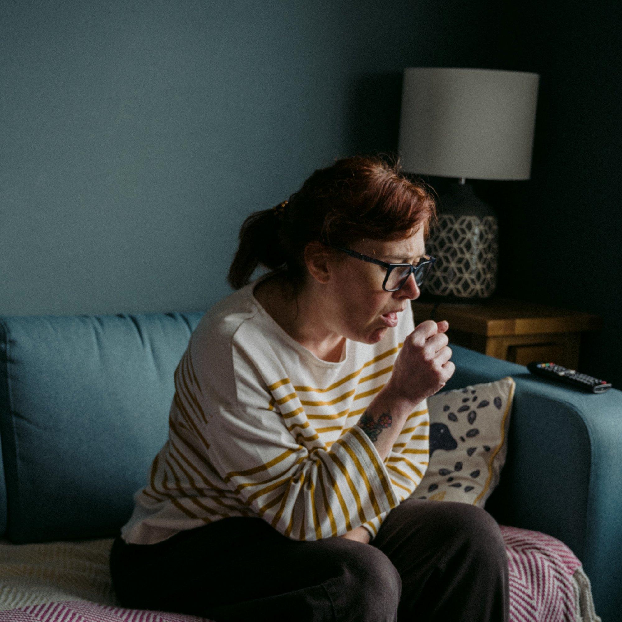 Frau auf Sofa, hustend